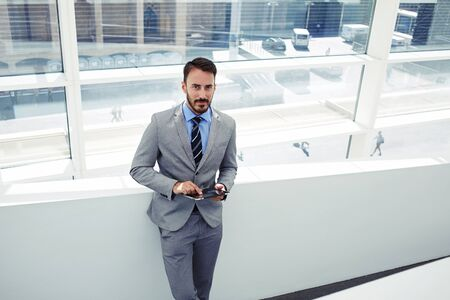 financier: Portrait of young successful man financier holding his touch pad while standing in modern office interior, prosperous male dressed in luxury corporate clothes using digital tablet during work break