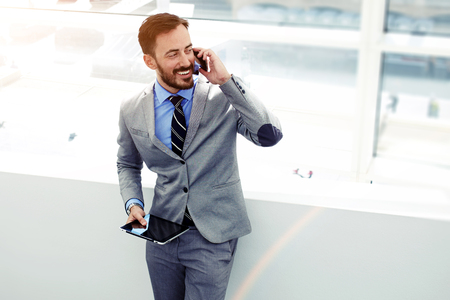 career success: Male economist talking on cell telephone while standing with touch pad in modern interior with copy space area, young successful men entrepreneur speaking on mobile phone during work on digital tablet