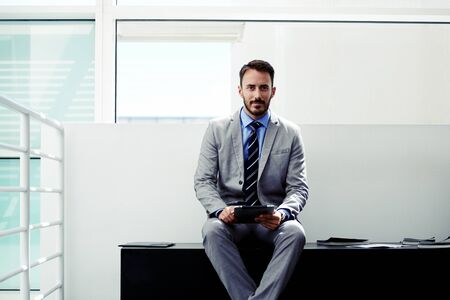 formal wear: Young skilled man lawyer in formal wear sitting with digital tablet in modern office space, confident male office worker dressed in corporate clothes using touch pad to prepare for important interview