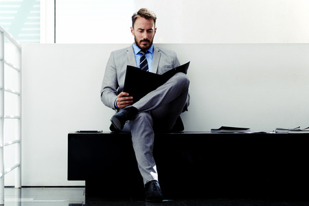 caucasian man: Portrait of a confident man entrepreneur studying important paper documents before business meeting, young seroius male dressed in elegant suit reading his portfolio before interview with employer
