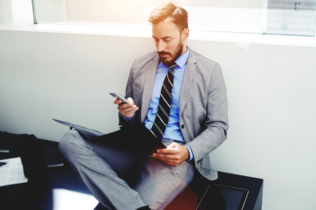 dossier: Portrait of skilled man office worker using cell telephone while sitting with paper documents in modern interior, confident male manager reading text on smart phone during studying dossier files