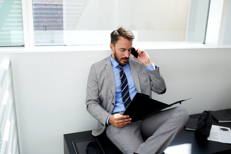 economist: Portrait of serious male economist dressed in corporate clothes talking on mobile phone while reading monthly reports, young businessman having cell telephone conversation while preparing for meeting