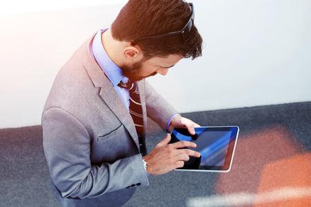 Vue de dessus d'un jeune homme ou gestionnaire d'entreprise en utilisant le pavé tactile pour se préparer à la journée de travail tout en se tenant à l'intérieur moderne de bureau, masculin qualifié habillé en costume de luxe travaillant sur tablette numérique avant de rencontrer