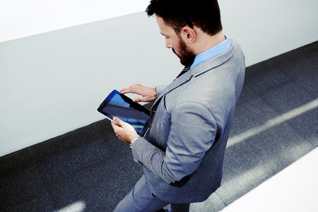 economist: View from above of a smart University Professor reading electronic book on touch pad before lectures, prosperous man economist holding digital tablet with copy space screen for your text or content Stock Photo