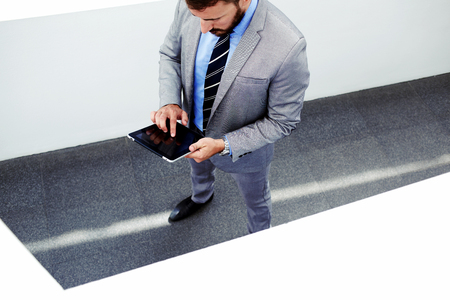 formal wear: Portrait of young confident man lawyer holding digital tablet with copy space screen for your promotional content, male managing director dressed in formal wear working on touch pad during work break Stock Photo
