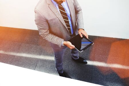 economist: Young businessman holding digital tablet with blank copy space screen for promotional content, skilled male economist dressed in corporate clothes using touch pad while standing in office interior