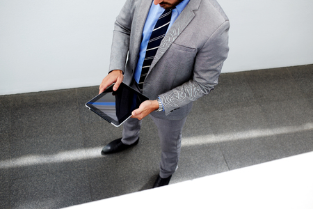 formal wear: Cropped shot view of a young man in suit holding touch pad with copy space for your text message or content, intelligent male professional banker in formal wear using digital tablet during work break