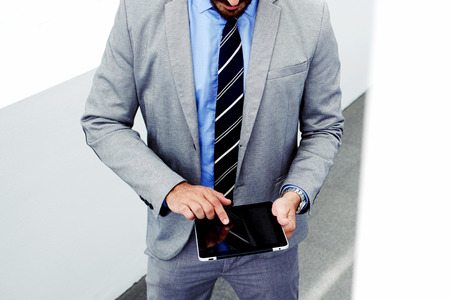purposeful: Cropped image with purposeful business man holding touch pad with copy space screen for promotional content, young male skilled managing director in luxury suit using digital tablet during work break Stock Photo
