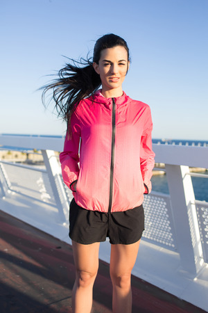 evening out: Half length portrait of young healthy female jogger dressed in colorful sportswear relaxing after workout out, beautiful fit woman resting after evening run in the fresh air during recreation time