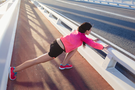 warm up exercise: Full length portrait of a brunette female runner dressed in bright sportswear stretching body muscles before start her jog, young athletic woman doing warm up exercise outside in sunny summer evening