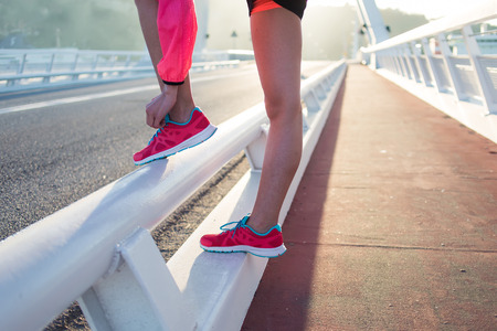 female jogger: Cropped shot view of female jogger tying laces on her colorful running shoes while relaxing after fit training outside, young athletic woman tie shoelaces while taking break between workout outdoors Stock Photo