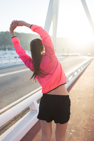 out of body: Back view of a young female jogger dressed in bright sportswear doing arms stretching exercise outdoors in summer day, athletic woman with perfect slim body working out while standing on running road Stock Photo