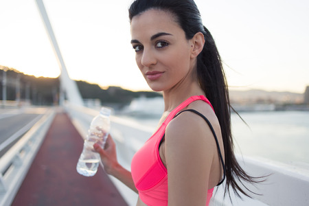 evening out: Cropped shot view of a young charming female jogger holding bottle of water while resting after active run outdoors, pretty athletic woman relaxing after workout out in summer evening outside Stock Photo