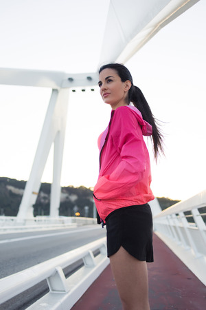 woman resting: Portrait of tired female jogger dressed in bright sportswear relaxing after evening run in the fresh air outside, young attractive athletic woman resting after physical activity during recreation time