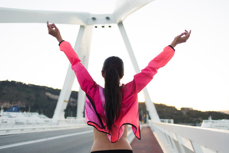 Back view of happy female with slender figure standing on a city bridge with raised hands while enjoying beautiful day after training, young sporty woman dressed in tracksuit relaxing after workout