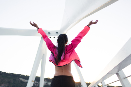 good evening: Back view of fit woman with slender body standing with raised hands felling freedom while rest after workout, young happy female enjoying good evening and weather after training in the fresh air Stock Photo