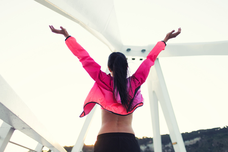 half dressed: Half length portrait of a fit woman dressed in colorful windbreakers standing with raised hands while relaxing after workout out, female runner enjoying beautiful day and rest after fitness training