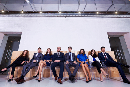 formal wear: Full length portrait of multi ethnic business people in formal wear waiting for start interview while sitting in corridor against wall background with copy space for your text message or advertising Stock Photo