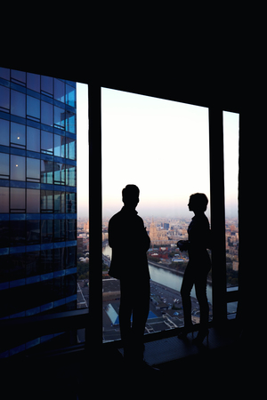 ceos: Silhouette of two confident colleagues having conversation while standing in corridor big company near window in evening time, young skilled workers discuss ideas after business meeting with partners