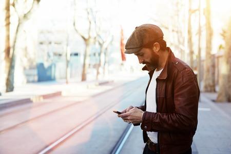 hombre con barba: retrato de medio cuerpo de hombre inconformista con barba vestido con ropa elegante charla en el teléfono celular mientras está de pie en la calle, varón de glamour con el uso fresco del estilo del teléfono inteligente durante un paseo al aire libre Foto de archivo