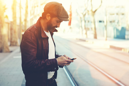Brustbild eines bärtigen Mannes mit Retro-Stil Zelle Telefon mit, während in der städtischen Einstellung, ein Mann in den stilvollen Kleidern auf Smartphone im Chat im kühlen Frühlingstag während des Gehens