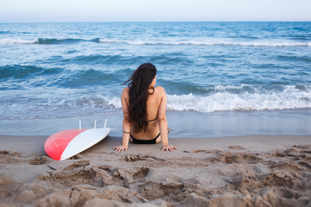 area sexy: Rear view of young surfer girl sitting on beautiful beach next to the sea,  young sportive female surfer observing tide waves and rest after surfing during summer vacation holidays, copy space area