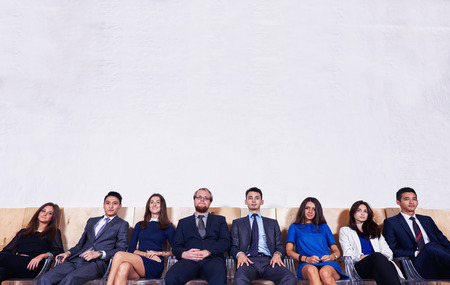 ceos: Portrait of a multi ethnic group of a confident business people in corporete clothes sitting in waiting room against wall background with copy space for your text message or promotion content
