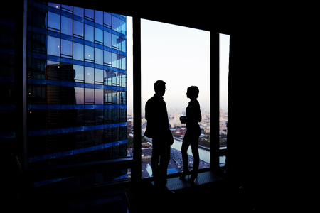 ceos: Silhouette of a couple of young business people having conversation while standing in hallway company near window, intelligent successful man and woman office workers discuss ideas during break
