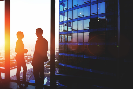 intelligent partnership: Silhouette of a two successful managing directors discuss ideas after meeting with partners while standing near big office window, young man and woman skilled economists relaxing after conference