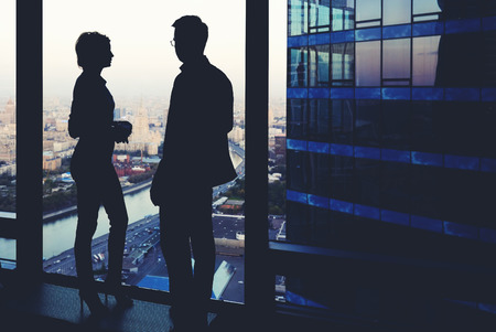 ceos: Silhouette of two business partners having conversation while standing near skyscraper window in modern interior with cityscape on background, young colleagues discuss ideas while rest after meeting
