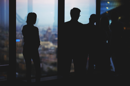 purposeful: Silhouette of a group young purposeful financiers lead a conversation while standing in modern office interior, confident partners talking among themselves while resting after business meeting
