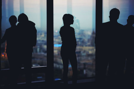 ceos: Silhouette of a young men and women office worker talking among themselves while they standing in office interior, successful partners discuss ideas during work break, confident colleagues at meeting Stock Photo