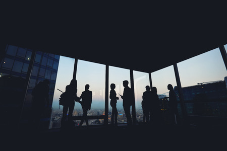 ceos: Silhouette of group of young skilled business people talking among themselves while standing in modern office interior near window, mans and womens purposeful bookkeepers discuss ideas after meeting Stock Photo