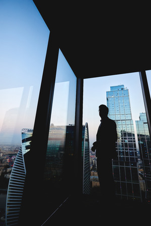 economist: Silhouette of a successful man economist resting after work day while standing near big office window in modern interior, male intelligent lawyer relaxing after meeting with his partners