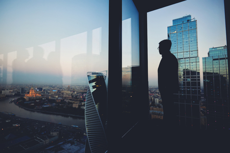 financier: Silhouette of a man financier think about something while standing near office window background with copy space for your text message or advertising content, young male thoughtful rest after briefing