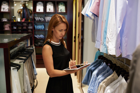 Portrait of a young woman seller using touch pad to check the prices for clothes while standing in fashion store, pretty female consultant working on digital tablet during job day in modern boutique