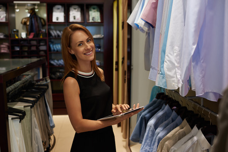 Half length portrait of happy female entrepreneur using digital tablet for job in her modern store with mens clothes, smiling woman owner or consultant holding touch pad while standing in brandy shop