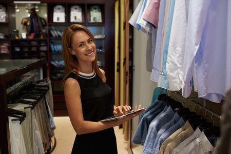 longueur mi-portrait de femme entrepreneur heureux utilisant tablette numérique d'emploi dans son magasin moderne avec des vêtements pour hommes, sourire femme propriétaire ou un consultant tenant pavé tactile tout en se tenant dans la boutique de brandy