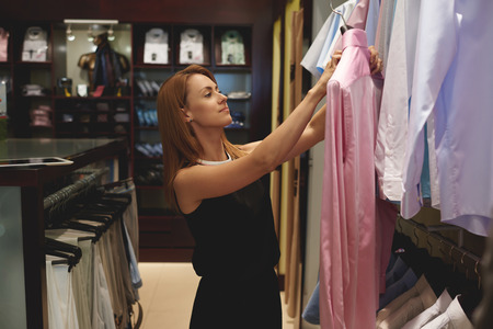 wealthy lifestyle: Half length portrait of a young beautiful woman buyer holding pink mens shirt while standing in modern shop interior, charming female consultant puts clothes in the fashion store during the work day Stock Photo
