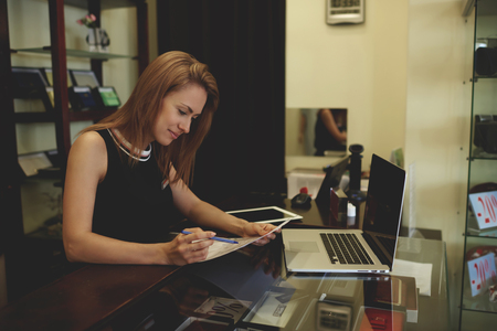 netbook: Young beautiful businesswoman or owner reading papers document during work on laptop computer while standing in her shop, pretty female entrepreneur using net-book while examines monthly reports