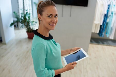 wealthy lifestyle: Half length portrait of happy woman consultant holding touch pad with copy space screen for your text message or advertising content, smiling female seller using digital tablet while standing in shop