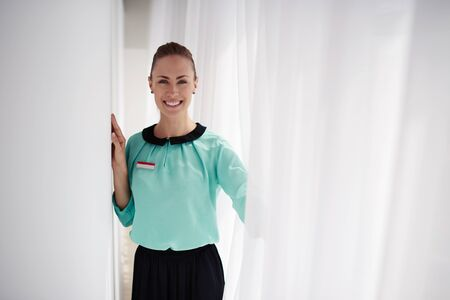 half dressed: Half length portrait of young charming woman consultant with beautiful smile posing, happy attractive female receptionist dressed in elegant clothes standing in modern hotel interior  with copy space
