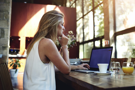 Portré, fiatal, gyönyörű nő, dolgozó, laptop számítógép, miközben ült a modern kávézó belső, szőke nő szabadúszó segítségével nettó könyv távoli munka során reggel reggeli kávézó