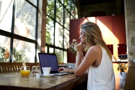 Vista trasera de una mujer joven rubia uso del teclado en el ordenador portátil con pantalla de espacio de la copia en blanco mientras se está sentado en el café, mujer inteligente estudiante de trabajo en red-libro después de sus conferencias en la Universidad Foto de archivo - 58106274