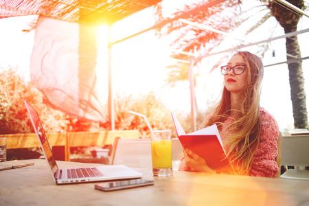 Portret van een slimme vrouwelijke student het lezen van boeken tijdens de vergadering in de voorkant open laptop computer in cafe bar in de frisse lucht, charmante vrouwelijke student rusten na het werk op de netto-book tijdens recreatie tijd Stockfoto