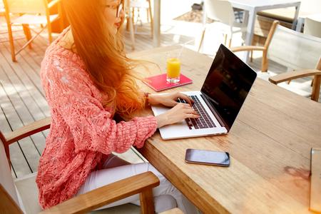 女性の若い魅力的な女性のコーヒー ショップで朝食中にネット書籍に取り組んでカフェ屋外に坐っている間コピー スペース スクリーンのラップトップ コンピューターのキーボードのトリミングされた画像 写真素材 - 58106400