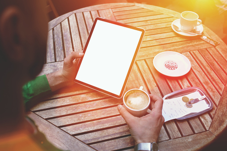electronic book: Cropped shot view of male holding touch pad with blank copy space screen for text message or advertising content, business man read electronic book during coffee break in sidewalk cafe in summer day