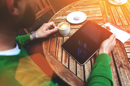 flare up: Cropped shot view of a businessman reading last news on touch pad during breakfast in sidewalk coffee shop, young man holding digital tablet with copy space screen for your text message or advertising Stock Photo