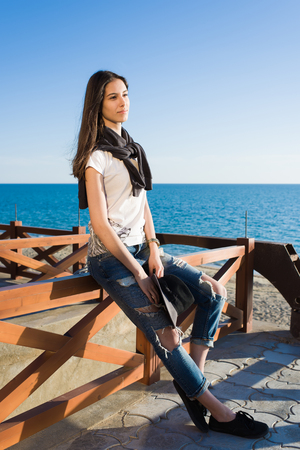 good weather: Charming young woman enjoying a good weather and recreation time while sitting against the sea in sunny afternoon, stylish female hipster rest after strolling along the beach in spring season