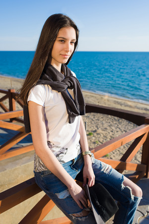 prettiness: Portrait of wonderful female enjoying sunny spring day sitting on the beach, attractive young woman dressed in stylish hipster clothes sitting against the sea during her recreation promenade Stock Photo